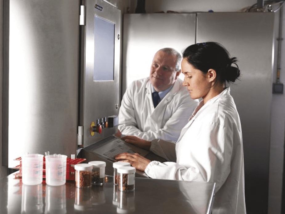 laboranci ubrani w białe kitle badający jakość karmy